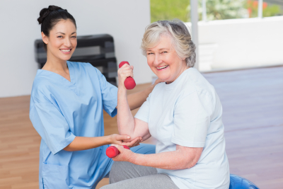 Portrait of female instructor assisting senior woman in lifting dumbbells at gym