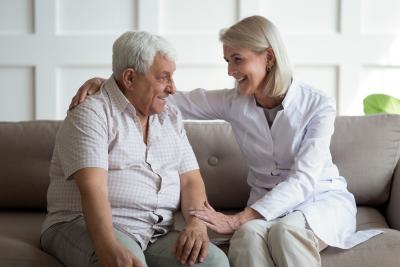 Smiling trustful middle aged doctor giving psychological help to elder man at home visit.